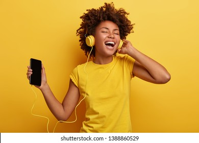 People, music, emotions concept. Delighted carefree female with Afro hairstyle dances in rhythm of melody, closes eyes listens loud song in headphones, holds smart phone has fun. Yellow color prevails