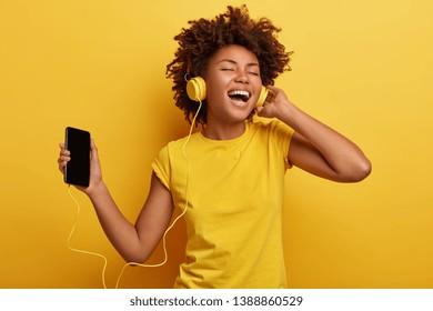 Menschen, Musik, Emotionen Konzept. Freuen Sie sich auf eine aufregende und sorgenfreie Frau mit Afro-Haarstil-Tänzen im Rhythmus der Melodie, schließt Augen lauscht Lied in Kopfhörern, hält Smartphone hat Spaß. Gelbe Farbe dominiert