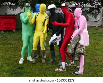 People at music festival in bright various coloured lycra body suits posing for a photograph.Wearing wellington boots and hats.