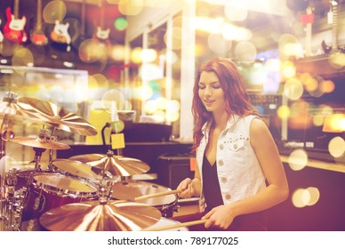 people, musical instruments and entertainment concept - smiling female musician playing drum kit at music store over lights