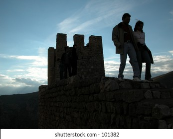 People near the city walls of the medieval town of Albarracin in the province of Teruel, Spain.