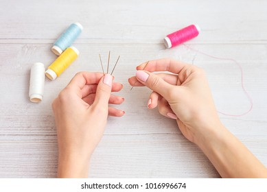 people, needlework, sewing and tailoring concept - tailor woman with thread in needle stitching fabric. Hands sewing with a needle and thread. Fingers pulling thread into the needle
