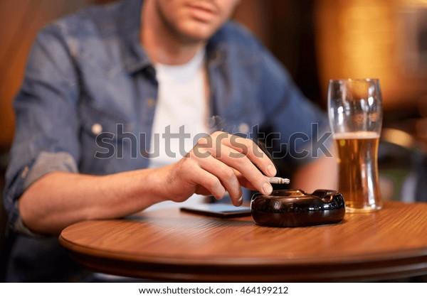 Menschen, Nikotinabhängigkeit und Konzept schlechter Gewohnheiten - Nahaufnahme von Menschen, die Bier trinken, Zigaretten rauchen und Asche zittern, um an Bar oder Kneipe Asche zu essen