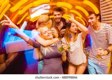 People in night club dancing, drinking and having fun