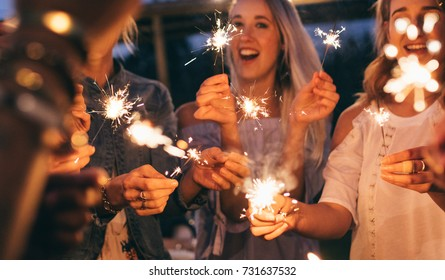 People at night holding sparklers. Group of friends enjoying with sparklers in evening.