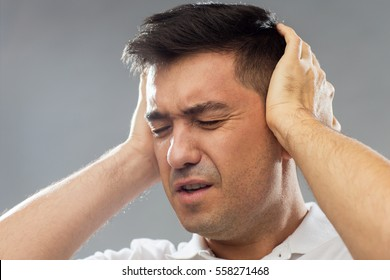 people, noise and stress concept - close up of unhappy man suffering from noise covering his ears with hands over gray background