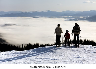 People observing mountain scenery. Family of three people stays in front of scenic landscape. These are skiers, they dressed in winter sport jackets and have skies attached