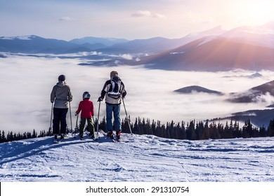 People observing mountain scenery. Family of three people stays in front of scenic landscape. These are skiers, they dressed in winter sport jackets and have skies attached.