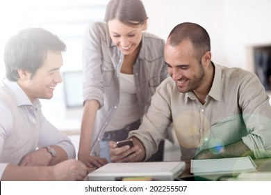 People in office laughing at reading text on smartphone