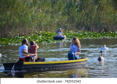 People in old boat by swans