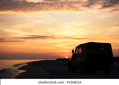 people on the beach at sunset time, parked car