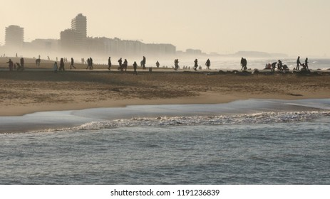 People on the Blankenberge beach, a Belgian coast, when the sun goes down and the wind is blowing  in December