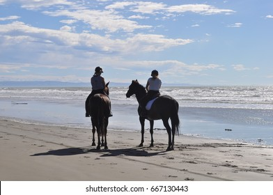 People on horses on the beach in Christchurch, New Zealand