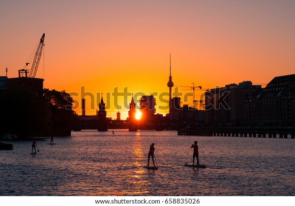 People on  paddle board / stand up paddler on river spree in Berlin - Oberbaum Bridge, Tv Tower and sunset sky background