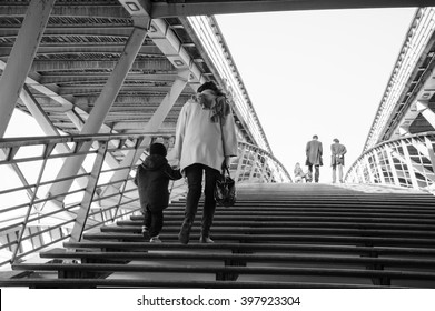 People on pedestrian Solferino bridge over Seine River near Orsey's Museum. Paris, France. Back view.