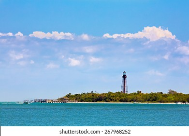 People on a pier, boats, and a sandy beach are backed by the brown metal tower of Florida's Sanibel Island Lighthouse and under a cloudy blue sky.