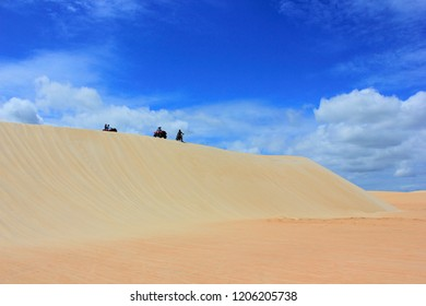 People on quadricycles and motorcycle on top of a steep dune in Jericoacoara, Ceará