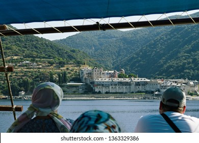 People on the ship looking at Dochiarien Monastery. Original touristic cruise ships in bay near Athos mount. Journey by ship to Mount Athos. Chalkidiki. Greece