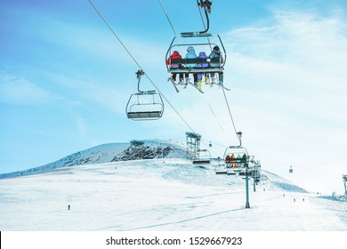 People on ski lift in winter resort - Holidays, snow gear renting, skiing, snowboarding and mountain landscape concept - Focus on guys sitting in cable car
