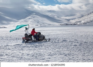 People on the snow sled on the frozen Cildir Lake (Cildir Golu) in Ardahan nearby Kars, Turkey