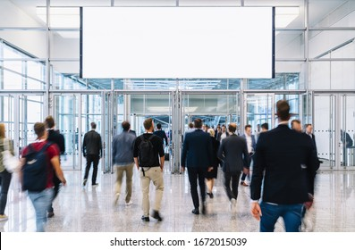 People on trade fair under advertising poster or banner