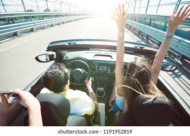 People on vacation on the road having fun driving a convertible car raising the arms to the sky