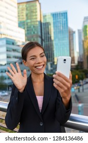 People on video call saying hello waving at camera. Asian woman video calling business partner on smartphone online in city street - Office buidlings on videochat call. Selfie entrepreneur cellphone.