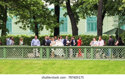 People are outside the fence in the park. St. Petersburg, Russia - 18 June, 2017. People at wedding events in the Summer Garden.