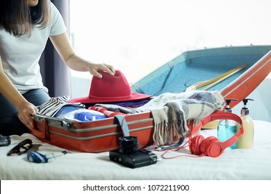 People packed suitcase with travel accessories on bed. Vacation concept