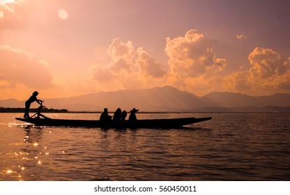 People paddle the boat in the lake with silhouette style.