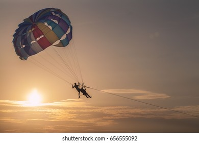 People parasailing over the sea with sunset.