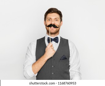 people, party and charity concept - happy young man with fake black moustache party prop