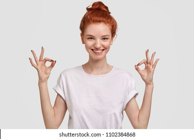 People, peace, body language and meditation concept. Cheerful freckled young female with glad expression, shows ok sign with both hands, dressd in casual white t shirt, demonstrates approval.