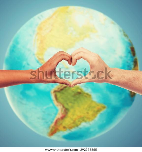 人、平和、愛、生命、環境のコンセプト – 地球の地球儀と青の背景に心の形のジェスチャーを示す人の手の接写