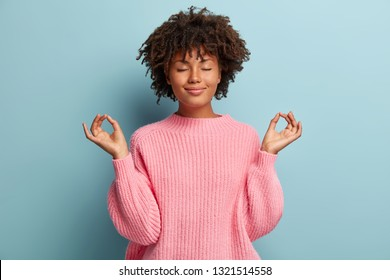People, peace and meditation concept. Calm black young woman practices yoga indoor, shows okay sign with both hands, demonstrates approval, wears pink clothing, isolated over blue background