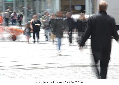 People in the pedestrian shopping zone, motion blur through long-term exposure, dangerous city life concept during coronavirus pandemic, copy space