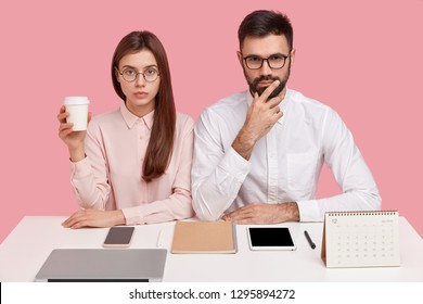 People, perfectionism and partnership concept. Serious woman and man office workers contemplate on future plans, think about startup, drink coffee from disposable cup, isolated on pink wall.