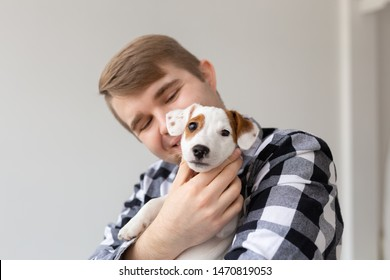 people, pets and animals concept - close up of young man hugging jack russell terrier puppy on white background