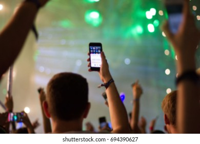 People with phones at concert, blurred background
