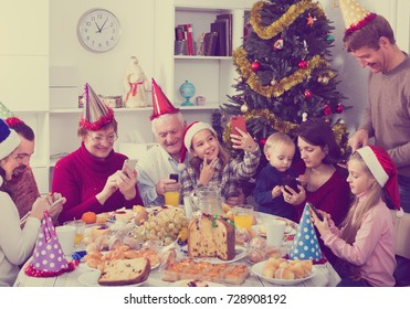 People are photo shooting best moments on their smartphones during celebration Christmas.