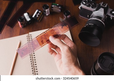 People picking film and background have a camera, film roll, book, pencil on wooden table.