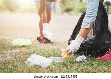 people picking up garbage and putting it in plastic black bag