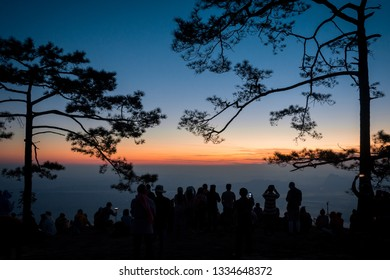 People and pine trees silhouette taken from Nok Aan cliff at sunrise, Phu Kradueng National Park, Loei Province