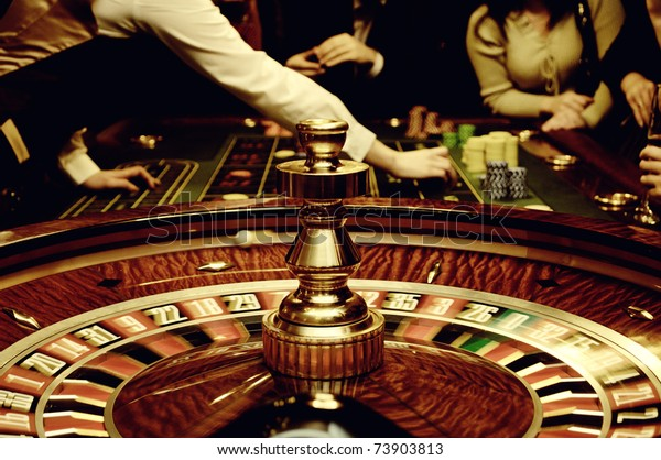People play casino games: gold spinning roulette with motion of players, croupier (dealer) and roulette in a modern casino. Selected focus used to accent the movement and game activity.