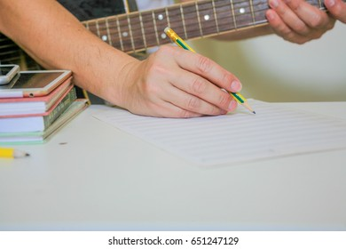 People play guitar and write notes on the table.