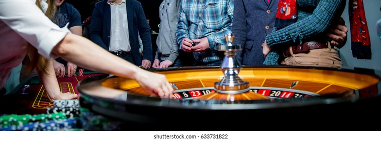 People play poker roulette at the table. Friends playing in the casino. A group of young people at a roulette table with a tape measure. Table for gambling in a luxury casino. Gambling.