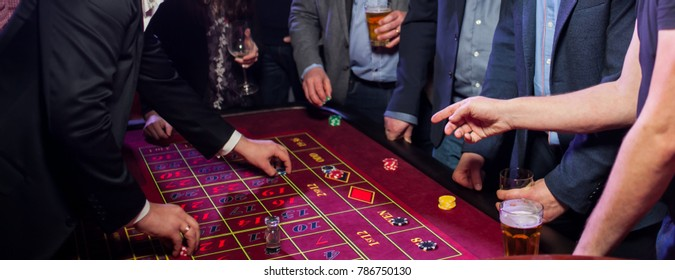 People play poker roulette at the table. Friends playing in the casino. A group of young people at a roulette table with a tape measure. Table for gambling in a luxury casino. Gambling.Casino roulette