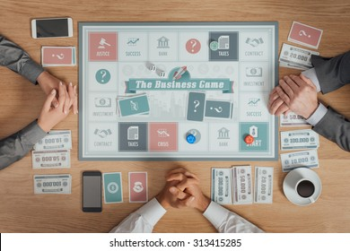 People playing a business board game on a wooden table, they are waiting with clasped hands, top view, unrecognizable people
