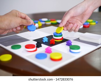 people playing fun board game on wooden table top selected focus