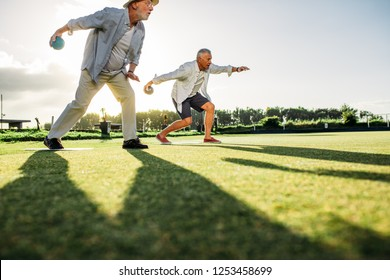 People playing a game of boules in a lawn with sun in the background. Two senior persons bending forward to throw  boules with their shadows on ground.